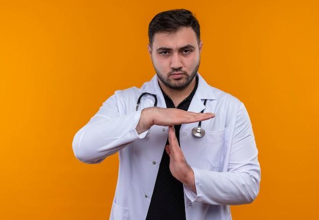 Gestörter junger bärtiger männlicher arzt, der weißen kittel mit stethoskop trägt und kamera unzufrieden betrachtet, die auszeitgeste mit händen macht