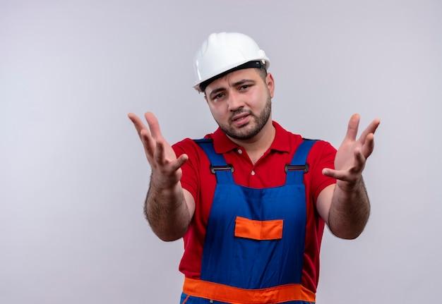Gestörter junger baumeister in bauuniform und schutzhelm, der hände hochhält und kamera unzufrieden ansieht