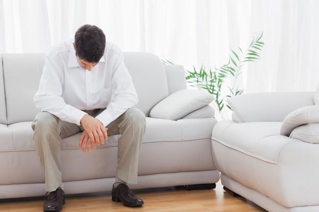 Gestörter junger mann, der auf sofa sitzt