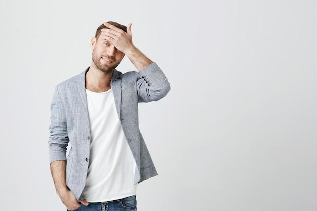 Gestörter junger mann gesichtspalme und blick gestört
