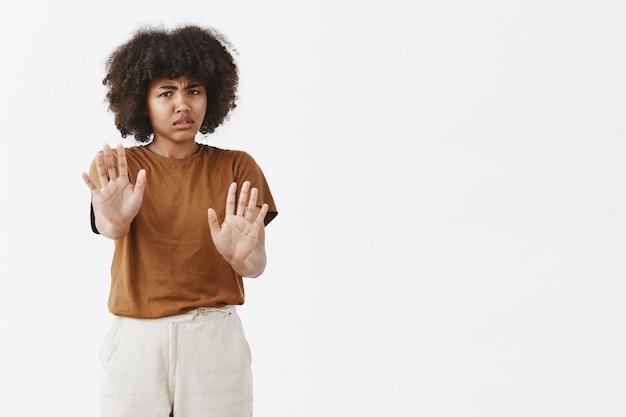 Gestörtes intensives zerstreutes junges afroamerikanisches mädchen mit lockigem haar, das hände in richtung schutzgeste zieht, die ablehnung oder ablehnung gibt