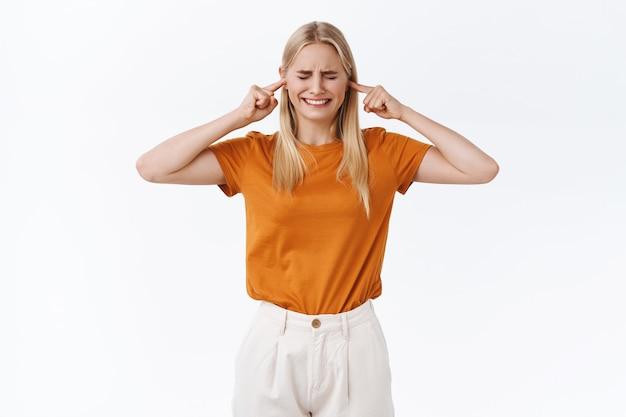 Gestörtes und verzweifeltes junges, modernes blondes mädchen kann sich nicht konzentrieren, schielen und pressen die zähne zusammen, verschließt die ohren vor lautem geräusch, verärgert die bauarbeiten der nachbarn, steht auf weißem hintergrund