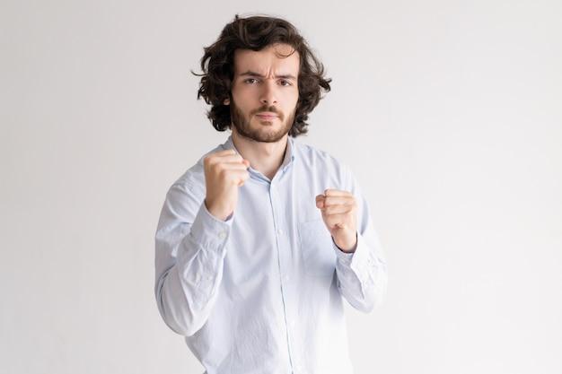 Gestraffter junger mann, der in der verpackenhaltung steht und kamera betrachtet
