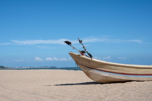 Gestreifte boote am strand angedockt, blauer himmel, meer und strand