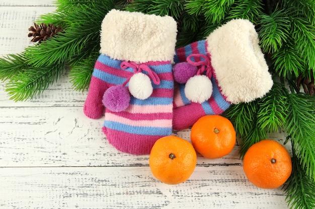 Gestreifte handschuhe mit tannenzweigen und mandarinen auf holzuntergrund wooden