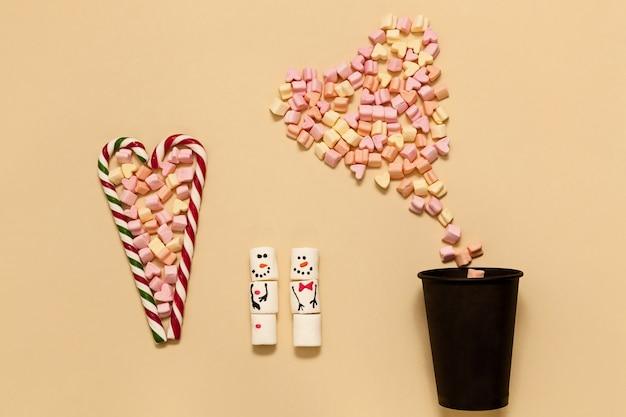 Gestreifte herzförmige lutscher mit marshmallows auf beigem hintergrund. schneemänner aus marshmallows