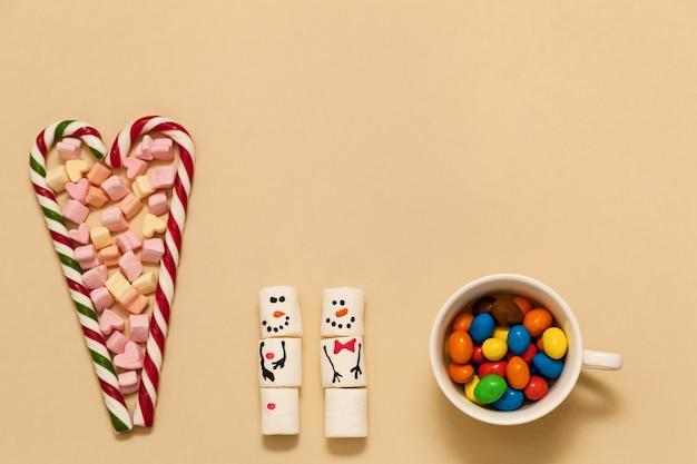 Gestreifte herzförmige lutscher mit marshmallows auf beigem hintergrund. schneemänner