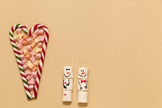Gestreifte herzförmige lutscher mit marshmallows auf beigem hintergrund.