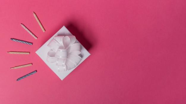 Gestreifte kerzen und geschenkbox auf rosa hintergrund