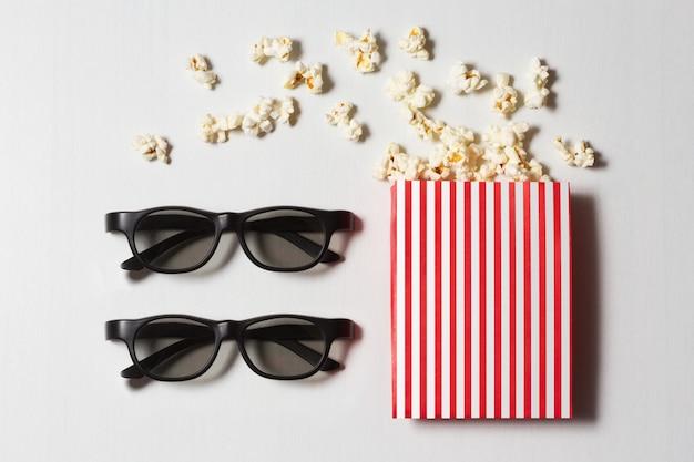 Gestreifte schachtel mit verstreutem popcorn und gläsern auf weiß