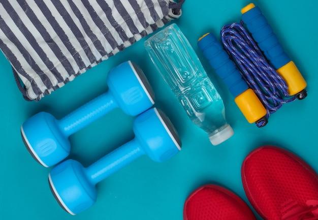 Gestreifte sporttasche mit sportoutfit und roten turnschuhen auf blauem hintergrund. sportstillleben. draufsicht.
