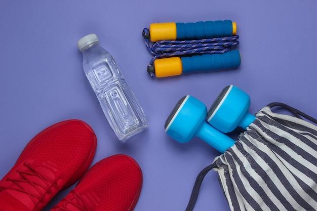 Gestreifte sporttasche mit sportoutfit und roten turnschuhen auf lila hintergrund. sportstillleben. draufsicht.