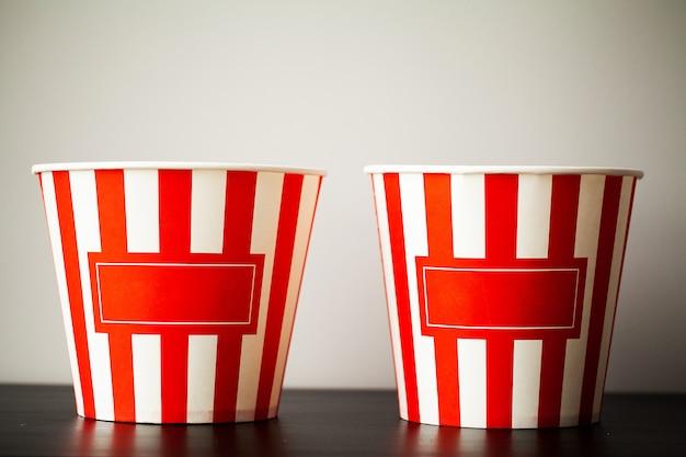 Gestreifter kasten mit popcorn auf hölzernem schreibtisch