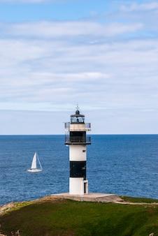 Gestreifter leuchtturm und segelboot