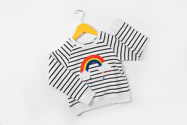 Gestreifter pullover mit regenbogen auf aufhänger auf weißem hintergrund. süßes kinderoutfit. kinderkleidung für herbst oder frühling.