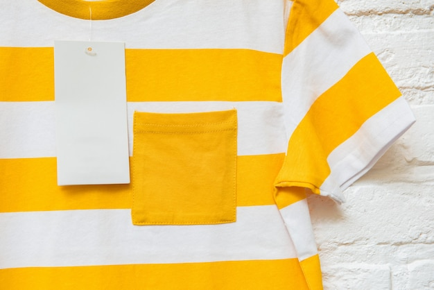 Gestreiftes gelbes und weißes t-shirt auf hellem hintergrund