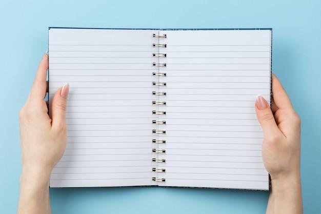 Gestreiftes notizbuch in den weiblichen händen auf einer blauen wand draufsicht, leerer schulnotizblock mit leeren seiten, flache lage.
