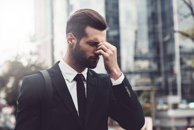 Gestresst und müde. frustrierter junger mann in festlicher kleidung, der seine nase massiert und die augen geschlossen hält
