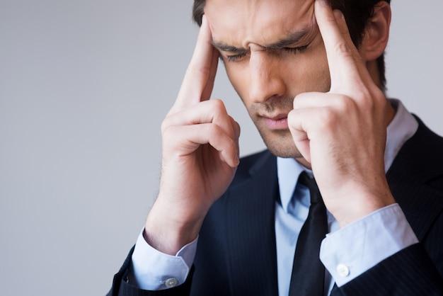 Gestresst und überarbeitet. frustrierter junger mann in formeller kleidung, der den kopf mit den fingern berührt