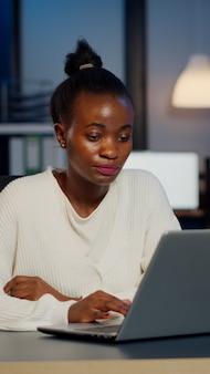 Gestresste afrikanische managerin, die mit finanzdiagrammen arbeitet, diagramme überprüft, auf dem laptop tippt, berichte spät in der nacht im start-up-büro liest und überstunden macht, um die projektfrist einzuhalten.