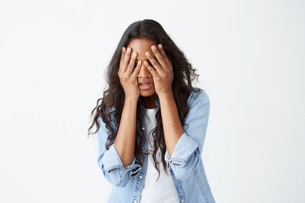 Gestresste afroamerikanische frau mit langen, welligen haaren, lässig gekleidet, verärgert, die hände auf dem kopf haltend und ihr gesicht verzweifelt versteckt, nachdem sie schlechte nachrichten gehört hatte.