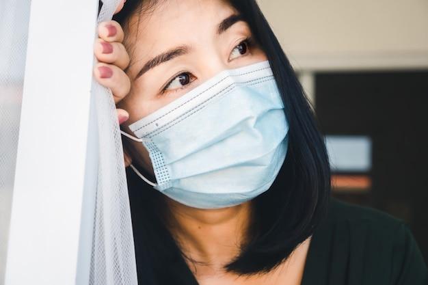 Gestresste asiatische frau, die gesichtsmaske selbstquarantäne zu hause trägt