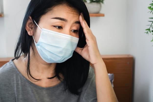 Gestresste asiatische frau mit schützender gesichtsmaske sorgen sich um krankheit