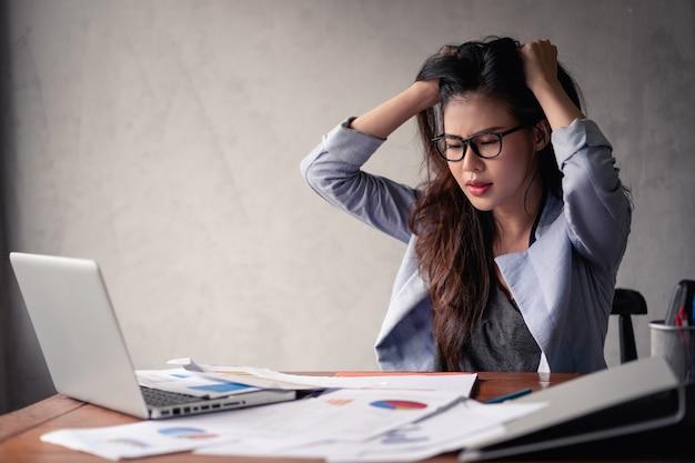 Gestresste asiatische geschäftsfrau, die laptop benutzt und arbeitet