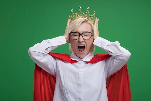 Gestresste blonde superheldin mittleren alters in rotem umhang mit brille und krone, die die hände auf dem kopf hält und mit geschlossenen augen isoliert auf grüner wand schreit
