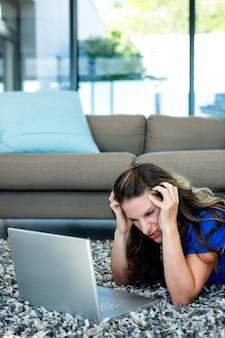 Gestresste frau, auf dem boden liegend und mit dem kopf in den händen auf ihren computer schauend