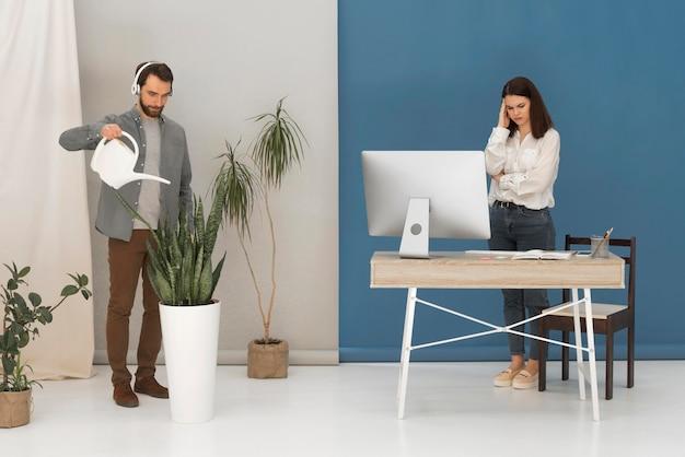 Gestresste frau, die am computer und am mann arbeitet, gießt pflanze