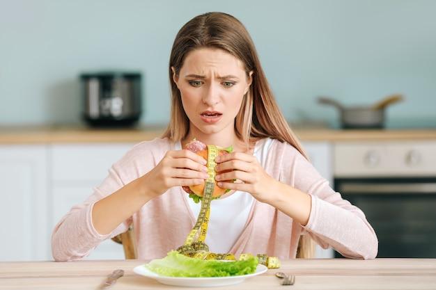 Gestresste frau, die ungesunden burger mit maßband in der küche hält. diätkonzept