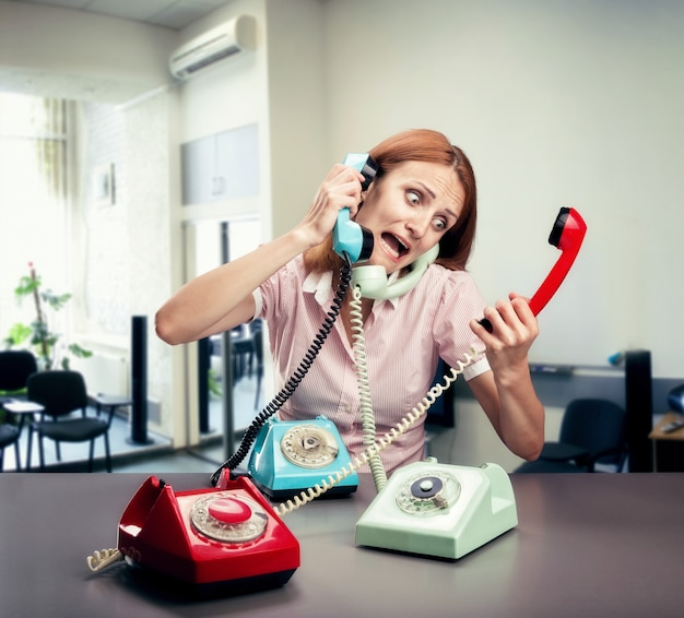 Gestresste frau mit drei telefonen