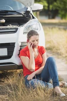 Gestresste frau sitzt am kaputten auto am straßenrand und telefoniert