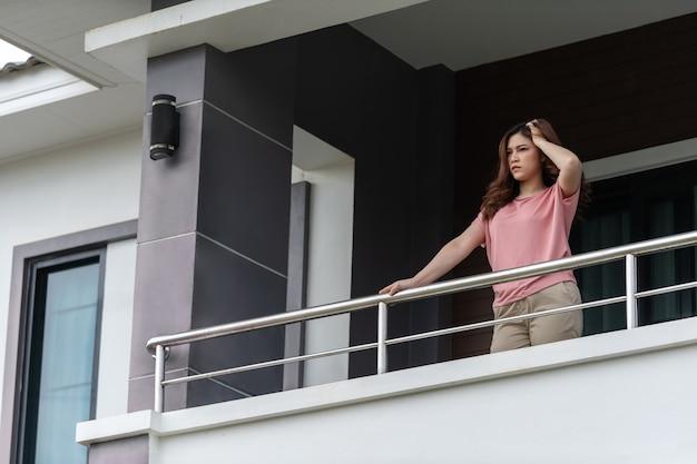 Gestresste frauenquarantäne auf dem balkon ihres hauses, konzept der coronavirus-pandemie