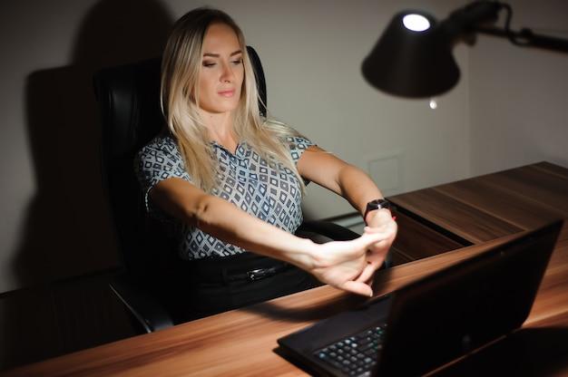 Gestresste geschäftsfrau, die am schreibtisch sitzt und über die lösung nachdenkt, während sie spät vor einem computer arbeitet.