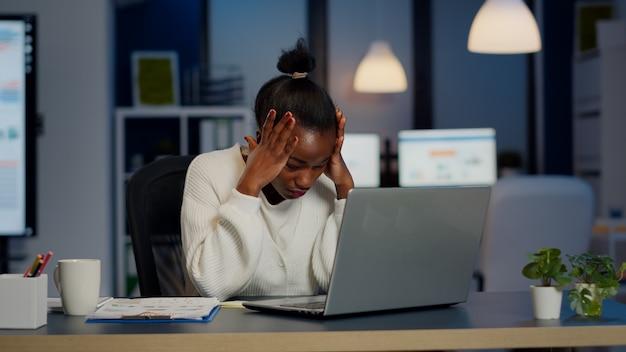 Gestresste geschäftsfrau, die bei der arbeit unter kopfschmerzen leidet, macht spät in der nacht überstunden