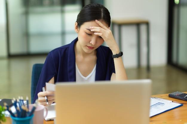 Gestresste geschäftsfrauen, die im büro arbeiten, sitzen vor dem laptop und denken nachdenklich, um probleme zu lösen Premium Fotos