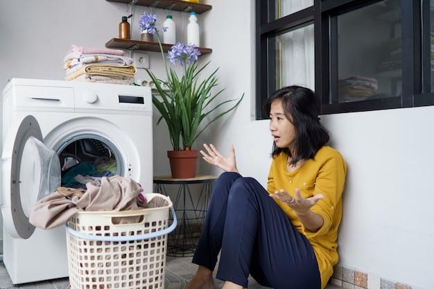 Gestresste hübsche asiatische hausfrau, die zu hause wäsche wäscht