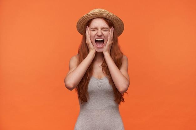 Gestresste junge angenehm aussehende rothaarige frau mit welligem langem haar, das über orange hintergrund in freizeitkleidung aufwirft, handflächen auf ihrer wange hält und mit geschlossenen augen laut schreit