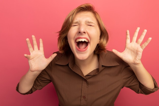 Gestresste junge blonde frau, die mit geschlossenen augen schreit und leere hände zeigt