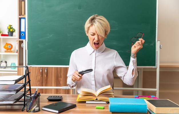 Gestresste junge blonde lehrerin, die am schreibtisch mit schulwerkzeugen im klassenzimmer sitzt und eine lupe über dem offenen buch hält, die brille abnimmt und mit geschlossenen augen schreit