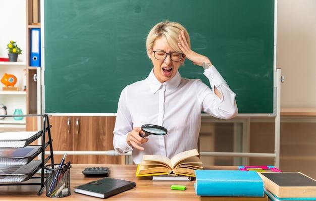 Gestresste junge blonde lehrerin mit brille, die am schreibtisch mit schulwerkzeugen im klassenzimmer sitzt und eine lupe über dem offenen buch hält, die hand auf dem kopf hält und mit geschlossenen augen schreit