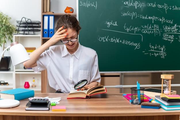Gestresste junge blonde mathematiklehrerin mit brille am schreibtisch sitzend mit schulwerkzeugen, die eine lupe halten, die hand auf offenem buch und auf dem kopf mit geschlossenen augen im klassenzimmer hält