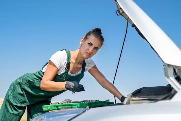 Gestresste junge frau, die den motor ihres autos betrachtet. probleme mit dem roadtrip. das auto braucht eine reparatur.