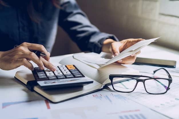 Gestresste junge frau, die rechnungen, steuern, bankguthaben überprüft und ausgaben im wohnzimmer zu hause berechnet