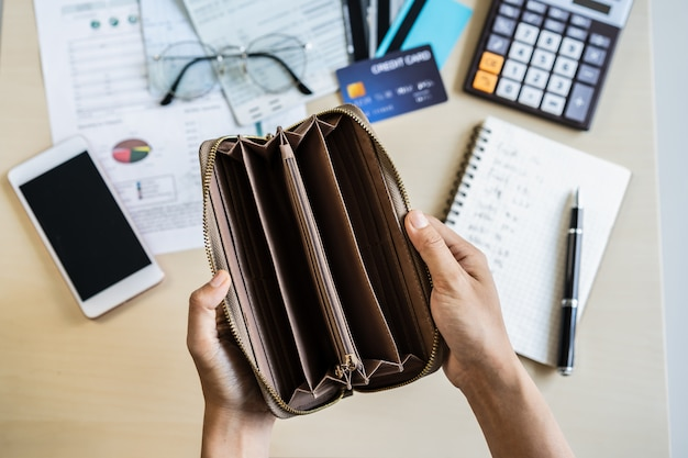 Gestresste junge frau öffnet ihre leere brieftasche und berechnet die ausgaben zu hause