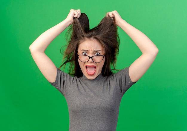 Gestresste junge hübsche frau, die brille trägt, die ihr haar lokalisiert auf grünem hintergrund zieht