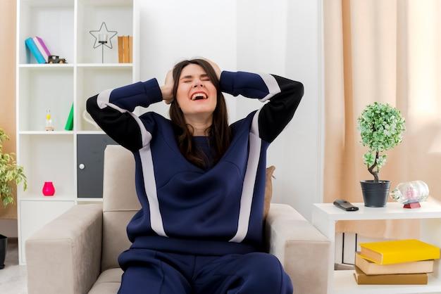 Gestresste junge hübsche kaukasische frau, die auf sessel im entworfenen wohnzimmer sitzt kopf hält und mit geschlossenen augen schreit