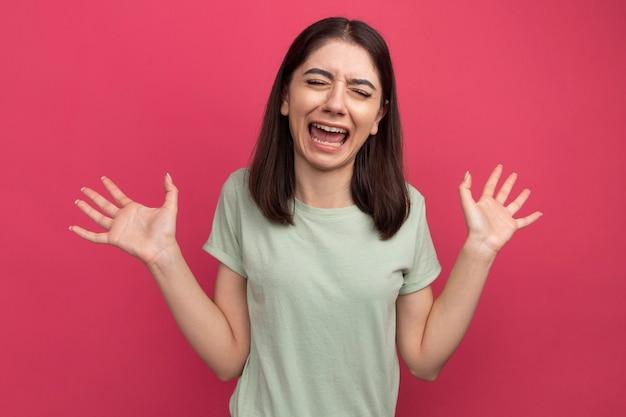 Gestresste junge hübsche kaukasische frau, die leere hände zeigt, die mit geschlossenen augen schreien
